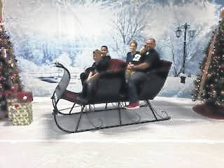 John and Mandy Nippert and their sons Levi, Isaiah and Samuel,seated in Santa's sleigh at the bazaar.