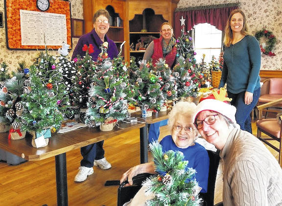 Pauline Collins, at left in front, with Dixie Shinaberry was the first to receive her Christmas tree at Morrow Manor in Chesterville. In back are Ann Vance, Jacqui Fatka and Jen Trainer.