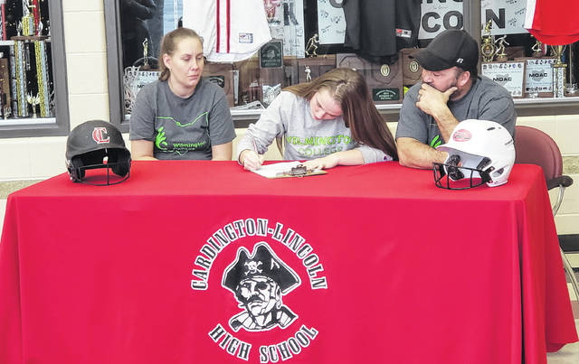 Cardington senior Taiylor Hubley signs her letter of intent to play softball for Wilmington College. Sitting with her are her parents, Jamie (l) and Jason Hubley.