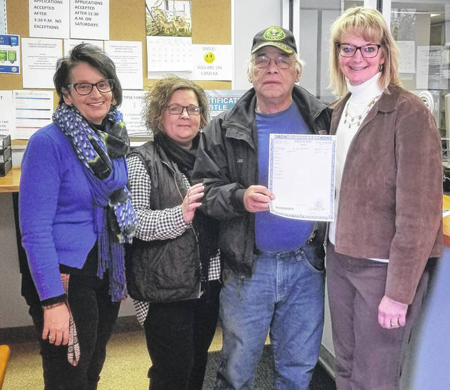 Shown, from left, are Title Deputy Clerks Sophia Watson and Kim Pfleiderer with customer Lon Combs and Clerk of Courts Kim Bood. Combs was the first to receive his car title in the new format.