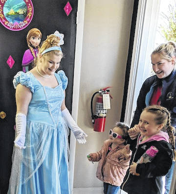 Cinderella brings smiles as she greets a family at Scoops Ice Cream Parlor.
