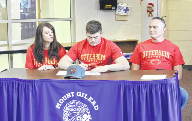 Garrett Casto (center) signs his letter of intent to play football for Otterbein University while his parents watch.