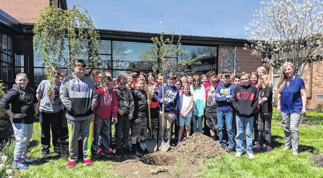 Kiwanis K-Kids with advisor Erin Kelty plant a weeping vherry tree at Park Avenue School in Mount Gilead April 22 as a service project for the school and community.