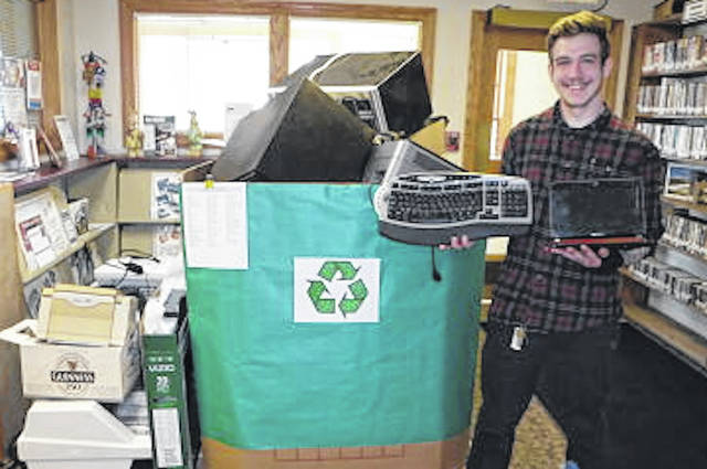 Marc Wells, digital literacy trainer, holds items recycled at the library.
