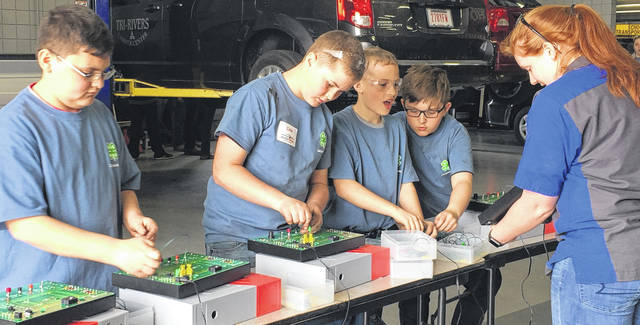 Evan Bowersmith, Cole Perkins, Dane Perkins and Parker Benner learn about the electronics of a car.
