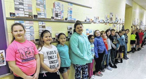 Third graders in Mrs. McElroy's third grade class stand beside their Shelfies in the hall.
