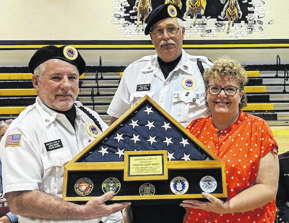 From left are veterans Gary Baker and Sam Beal from AMVETS Post 87 presenting the flag to high school English teacher LaNeta Wertz for Northmor being number one in the nation for their correspondence with military and veterans.