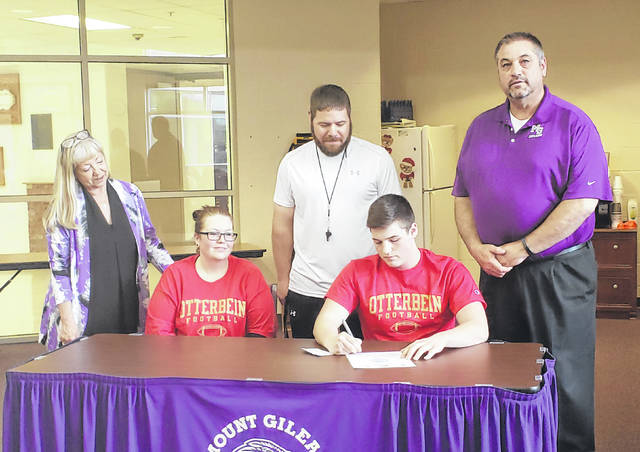 Mount Gilead High School football player Tristin Seitz signs his letter of intent to play for Otterbein University. Sitting next to Seitz is his mother, Brittany. In the back row are (l-r): MGHS principal Deb Clauss, football coach Joe Ulrey and athletic director Dave Logan.