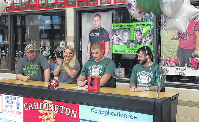 Cardington senior football player Deven Speck signs to play football for Wilmington College. In the picture are (l-r): step-father Jeremy Clark, mother Rachel Clark, Steck and father Mark Speck.
