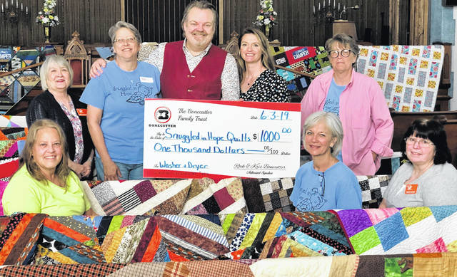 Rockwell and Krista Bonecutter presented a $1,000 check to Snuggled in Hope Quilts. On hand to accept the donation were Cheryl Jason, board members Mary Siegfried, Kim Porter, President Kyle Huvler, Penny Reeve and Vickie Zoulek.