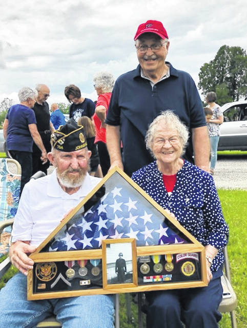 Duane Rinehart is seated with his sister Marilyn Sipes. Standing is his brother Dan Rinehart. He is holding the honors box that was assembled by the Color Guard in his honor.