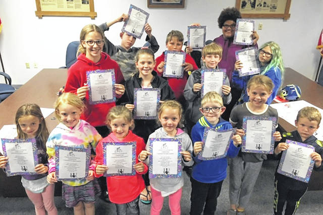 Shown are Kids in the Park holding gift certificates from Morrow Lanes allowing them to have one free game of bowling shoe rental and pizza.