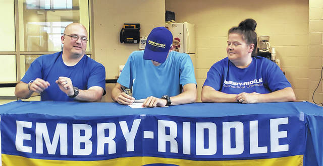 Connor Page (center) signs his letter of intent to compete on the Embry-Riddle Aeronautical University track and field team. Sitting with Page are his parents, Scott and Donna.