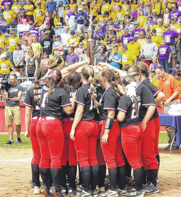 The Cardington softball team raises their Division III state runner-up trophy after their game with Warren Champion on Saturday.