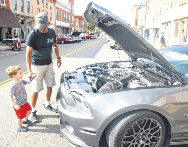 The Mount Gilead Merchants Association sponsored a car show Friday evening on South Main Street. Bruce McChesney and grandson Harrison Wyeth look at his 2014 Shelby GT500.