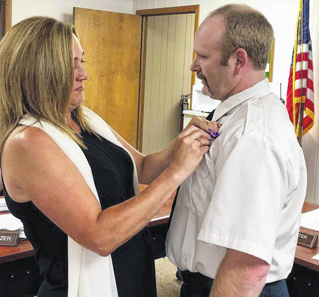 Chad Swank was sworn in as village of Mount Gilead fire chief. Wife Monica places his chief's pin on him Monday night.