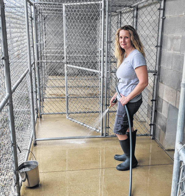Morrow County Dog Warden Sarina Atwell with Zeus, a black Shar-Pei and pit bull mix, at the Morrow County Dog Shelter. Kim Piatt works to keep the Morrow County Dog Shelter clean so that dogs remain healthy.