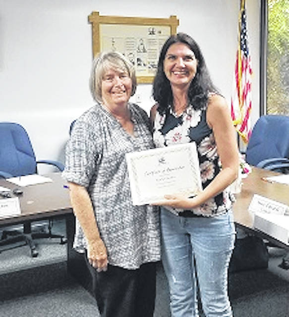 Cardington Mayor Susie Peyton, left, presents a certificate of appreciation to Heather Deskins, right, who has moved from the area resulting in her resignation from Cardington council, a seat she has held for six years. She was honored during the village council meeting Aug. 19.