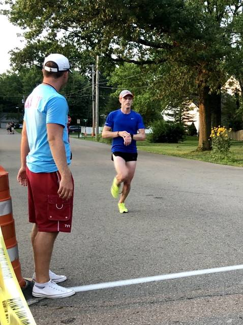 Jake Hayes crosses the finish line first in the Dash at Dusk last week. Runners take part in the fun run.