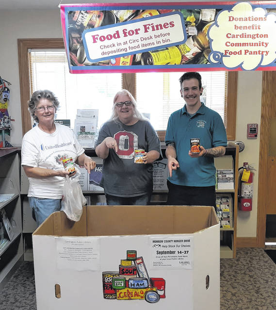 Ready to receive non perishable food items at the Cardington Public Library are, from left, Jean Smith, Kelly Kirkpatrick and Ian Ferguson.