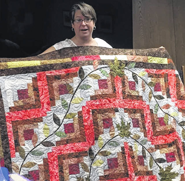 Robin Jordan of Thread, White & Blue shows one of her quilts to the Mount Gilead Kiwanis Club Wednesday. She operates the business from her home near Chesterville. Jordan can be reached at threadwb@gmail.com; her website is threadwhiteblue.com.
