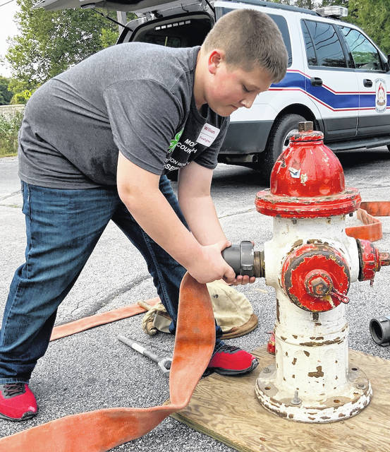 William Huddleston connecting a fire hose to a fire hydrant as fast as he can and then simulating turning it on.