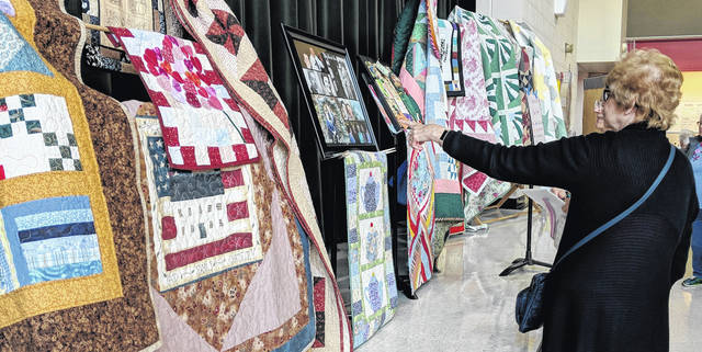 Patti Feustal points out a special quilt to Susan Keightley as they look at Distinguished Quilter Kathy Friend's quilts.