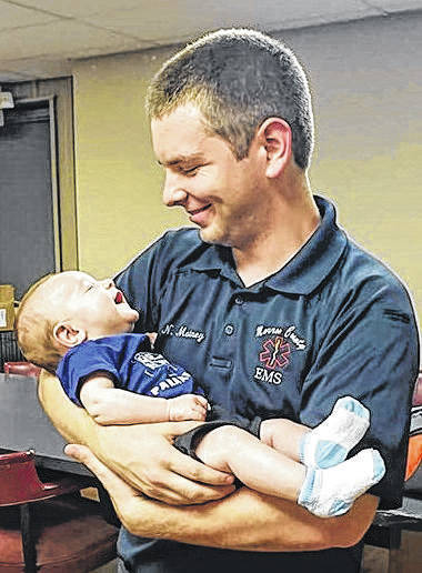 Baby Levi held by Nathan Matney, an EMT who assisted with his delivery on June 22.