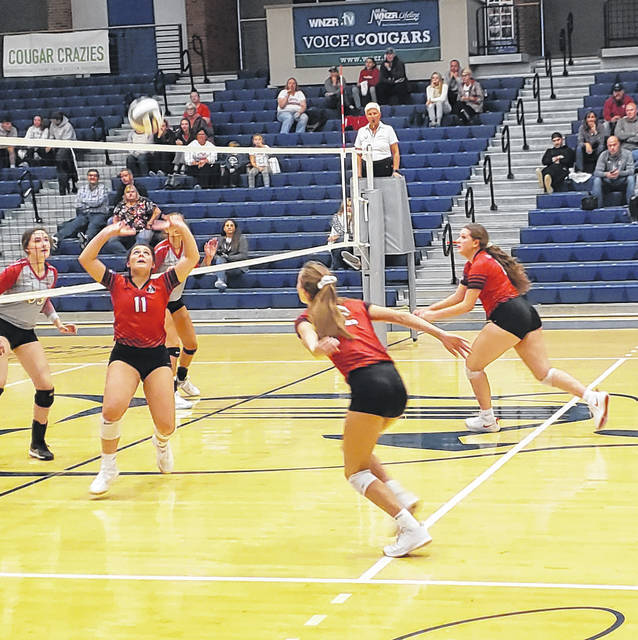 Cardington's Kyleigh Bonnette sets the ball, while teammates Izzy Wickline (foreground) and Ashlee Tharp get in position for kill attempts.