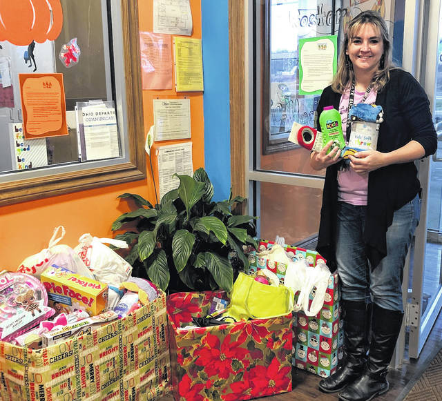 Director Holly Schade of Karen's Kids Campus shows the items collected that will go to the Family and Children Services foster care program.