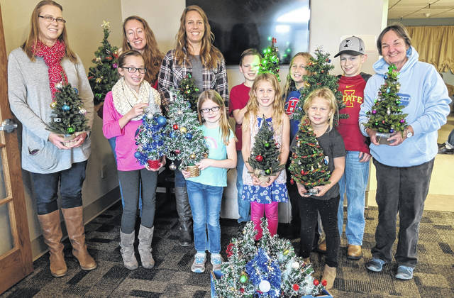 """Christmas angels"" who brought trees and sang carols at Woodside Village Care Center are back, from left: Jacqui Fatka, Julie McLeod, Spencer Fatka, Kayla Trainer, Josiah Fatka and Dixie Shinaberry. In front are: Kayla McLeod, Avonell Fatka, Mallory Trainer and Julie Trainer."