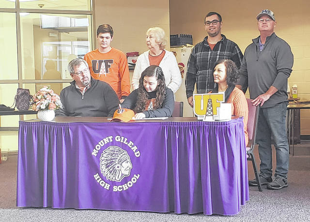 Mount Gilead senior Mallory Graham signs her letter of intent to play golf for the University of Findlay. Sitting with her are her parents, Matt and Robyn. In the back row are (l-r): boyfriend Mitchell, grandmother Vicky Ruhl, brother Gavin and Mount Gilead golf coach Trent Kincade.