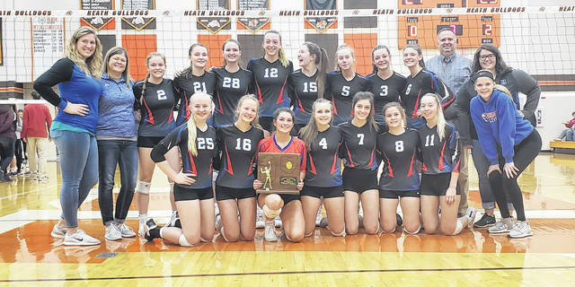 Highland's volleyball team celebrates with their regional championship trophy after dispatching Dover in three sets to make it to the Division II Final Four.