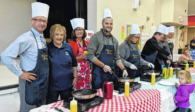 Celebrity chefs, from left: Brandon Moore, Lisa Tharp, Williamsport Grange member, Joanne Trainer, Brandon Hayes, Municipal Court Judge Jenifer Burnaugh, Andy Bower, Morrow County Sheriff John Hinton and Allen Stojkovic. Dave Burnaugh and Addison are waiting for Jenifer to finish their omelettes.