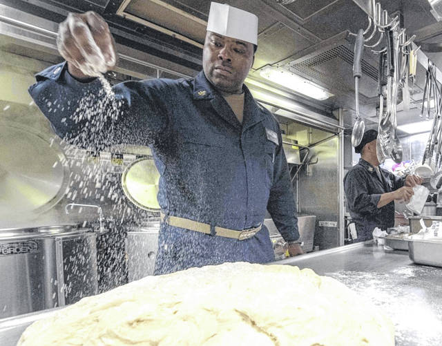 Senior Chief Culinary Specialist Reggie Leake, from Mount Gilead, sprinkles flour on dough aboard the Arleigh Burke-class guided-missile destroyer USS Paul Hamilton (DDG 60) before Thanksgiving dinner Nov. 28. Paul Hamilton is under way conducting routine training in the Eastern Pacific Ocean.
