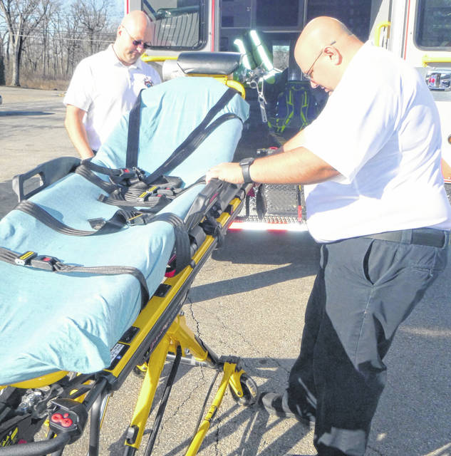 Morrow County EMS Captain Jeremiah Woodmansee, right, shows the features of one of the new Power Lift Cots that were acquired through a federal grant. Mickey Smith, president and CEO of Ohio First Responder Grants, LLC, looks on.