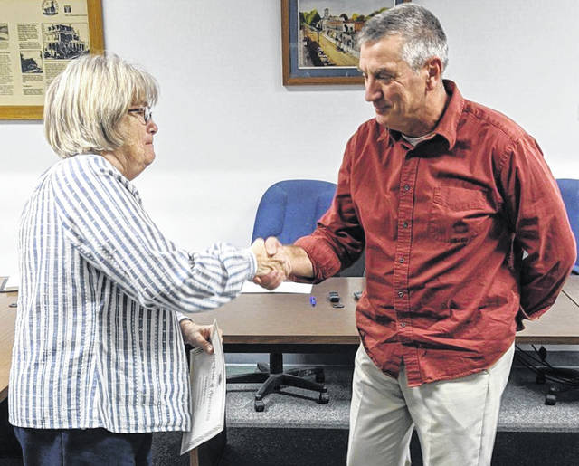 Cardington Mayor Susie Peyton congratulates council member Tim Abraham at the conclusion of his last meeting as a council member. Abraham has served two separate full terms.