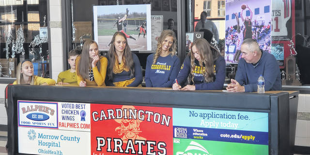 Surrounded by her family, Cardington's Casey Bertke signed to play both women's basketball and softball for Cedarville University on Wednesday. From left to right are Jill, Blake, Dana, Megan, Jennie, Casey and Ben Bertke.