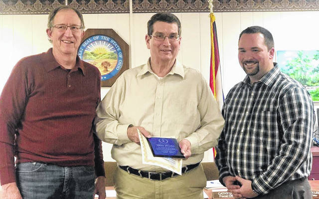 Outgoing mayor Mike Porter, center, received a certificate of appreciation and a plaque at the village council meeting Jan. 21. Shown are council president Tim Clapper, left, and Mayor Jamie Brucker.