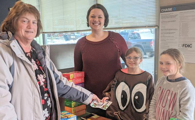 """Stocking up on Girl Scout cookies are Sherrie Them, left, with Lindsay Lester, Reagan Lester, and Bella Wingert. Reagan is giving Them certificates for buying five boxes or more. It's called """"5 for Five"""" customer contest."""