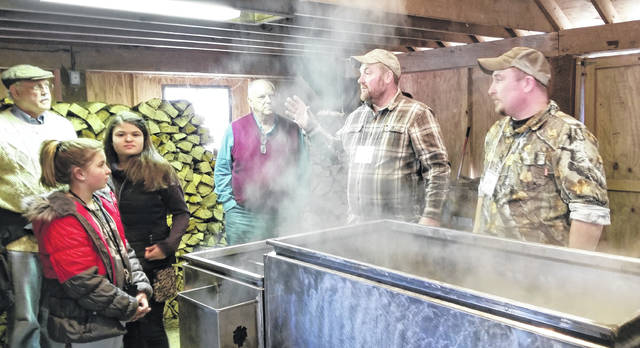 Eric Baldinger and Cody Miller teaching a group of visitors to the LMC Maple Syrup Festival how the sorghum is heated in the kettle over a hot fire and results in maple syrup. Miller said he has been teaching people about the process for about six years. He noted that changes through the season determine if the syrup will be lighter or darker in its cooking process.