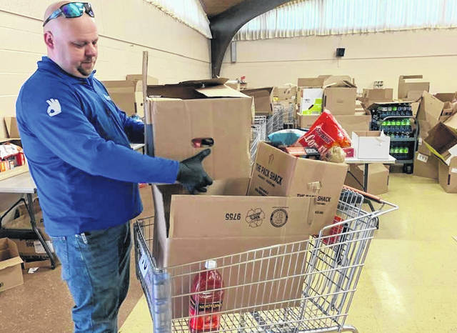 Chris Toombs loads a grocery cart at First United Methodist Church in Cardington's food pantry Wednesday morning.