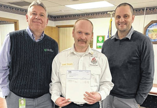 Bob Boss (left) and Brandon Hayes of First-Knox National Bank present a check for $2,944.35 to village Fire Chief Chad Swank. It is to purchase a defibrillator.