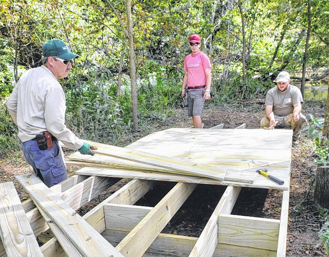 Volunteers work to repair a bridge at Fishburn Reserve Park. From left are Chris Robinson, Dustin Robinson and Zack Robinson.