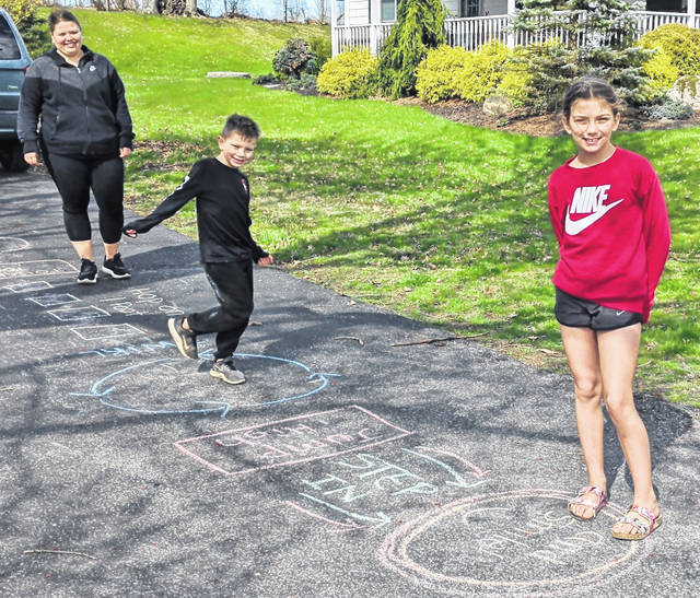 Mount Gilead Middle School science teacher Danielle Bault enjoys the sunshine and hopscotch with her children Jackson and Bailey. Grant Street driveway hosts hopscotch game.