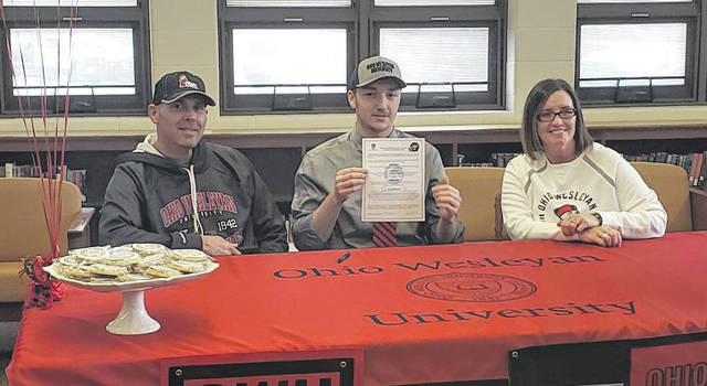 Northmor senior Hunter Mariotti (center) holds up his letter of intent to play football for Ohio Wesleyan University. Sitting with Mariotti are his parents, Doug and Jenny.