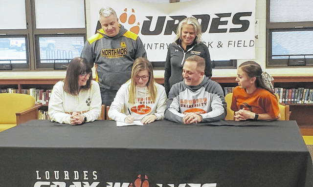 Northmor senior Juliana DiTullio (front, second from left) signs her letter of intent to run both cross country and track and field for Lourdes University. In the front row with her are, left to right, mother Kris, father Tony and sister Isabelle. In the back row are Northmor cross country and track coach Mark Yaussy and Lourdes cross country and track coach Cheryl McLean.