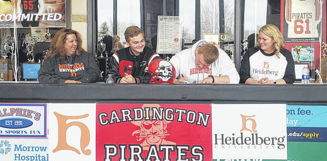 Nick McAvoy of Cardington (second from right) signs his letter of intent to play football for Heidelberg. With the Pirate senior are (l-r): stepmother Jeaneen McAvoy, brother Colin McAvoy and mother Susan McAvoy.
