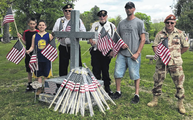 Courtesy Photo Placing flags at Rivercliff Cemetery are, from left: Dominic Hester, Mason Hester, Steve Montell, Dan Fricke, Erick Shaffer and Frank Moore.