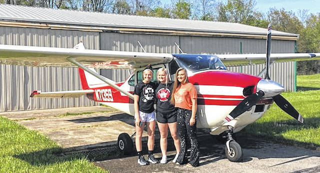Cardington-Lincoln High School seniors, from left, Emily Benson, Baylee Adams and Kiersen George, who just finished a Fly-By Friday flight.